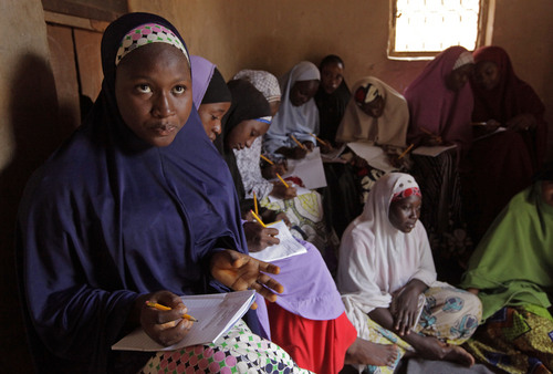 In this Monday, June 2, 2014 photo, Maimuna Abdullahi, left, writes down information from the blackboard as she and others attend school in Kaduna, Nigeria. Maimuna wore the scars of an abused woman anywhere: A swollen face, a starved body, and, barely a year after her wedding, a divorce. But for Maimuna, it all happened by the time she was 13. Maimuna is one of thousands of divorced girls in Nigeria who were married as children and then got thrown out by their husbands or simply fled. (AP Photo/Sunday Alamba)