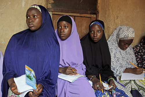 In this Monday, June 2, 2014 photo, Maimuna Abdullahi, left, listens during class as she and others attend school in Kaduna, Nigeria. Maimuna is one of thousands of divorced girls in Nigeria who were married as children and then got thrown out by their husbands or simply fled. (AP Photo/Sunday Alamba)