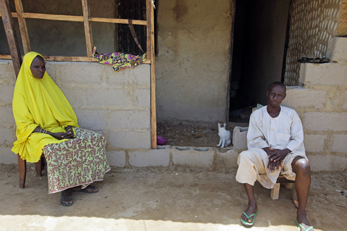 In this Monday, June 2, 2014 photo, Rabi Abdullahi, left, sits with her husband, Haruna Abdullahi, outside their home in Kaduna, Nigeria. They are the parents of Maimuna Abdullahi. Maimuna wore the scars of an abused woman anywhere: A swollen face, a starved body, and, barely a year after her wedding, a divorce. But for Maimuna, it all happened by the time she was 13. Maimuna is one of thousands of divorced girls in Nigeria who were married as children and then got thrown out by their husbands or simply fled. (AP Photo/Sunday Alamba)
