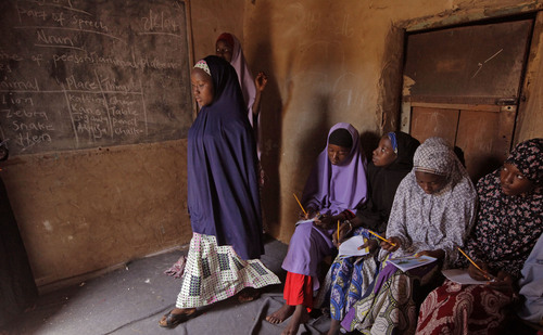 In this Monday, June 2, 2014 photo, Maimuna Abdullahi, left, moves toward the blackboard during class as she and others attend school in Kaduna, Nigeria. Maimuna wore the scars of an abused woman anywhere: A swollen face, a starved body, and, barely a year after her wedding, a divorce. But for Maimuna, it all happened by the time she was 13. (AP Photo/Sunday Alamba)