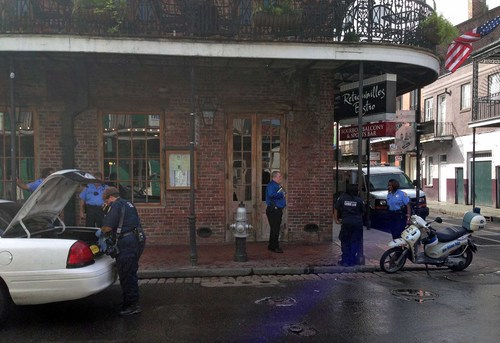 After a shooting on Bourbon Street, an apparent gunshot hole is seen in a door of the Bourbon Heat night club, as one employee sweeps up the sidewalk outside, early Sunday, June 29, 2014, in New Orleans. Nine people were shot on Bourbon Street in New Orleans' celebrated French Quarter, leaving at least one person in critical condition. (AP Photo/NOLA.com/The Times-Picayune, Benjamin Alexander-Bloch) MAGS OUT; NO SALES; USA TODAY OUT; THE BATON ROUGE ADVOCATE OUT