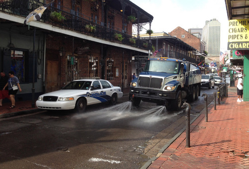 A Progressive Waste Solutions truck sprays along Bourbon Street, following a shooting earlier in the day, Sunday, June 29, 2014, in New Orleans. Nine people were shot on Bourbon Street in New Orleans' celebrated French Quarter, leaving at least one person in critical condition. (AP Photo/NOLA.com/The Times-Picayune, Benjamin Alexander-Bloch) MAGS OUT; NO SALES; USA TODAY OUT; THE BATON ROUGE ADVOCATE OUT