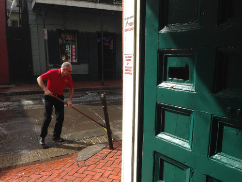 After a shooting on Bourbon Street, an apparent gunshot hole is seen in a door, at right, of the Bourbon Heat night club, as one employee sweeps up the sidewalk outside, early Sunday, June 29, 2014, in New Orleans. Nine people were shot on Bourbon Street in New Orleans' celebrated French Quarter, leaving at least one person in critical condition. (AP Photo/NOLA.com/The Times-Picayune, Benjamin Alexander-Bloch) MAGS OUT; NO SALES; USA TODAY OUT; THE BATON ROUGE ADVOCATE OUT