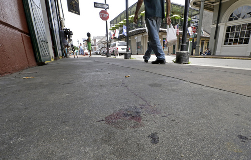 Blood stains are seen on the sidewalk at the scene of a shooting that happened early Sunday morning, June 29, 2014, on Bourbon Street in New Orleans. Nine people were injured, one seriously, according to New Orleans Police. (AP Photo/Gerald Herbert)