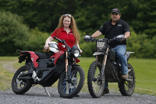 Maggie McNally-Bradshaw and her husband Curt Bradshaw pose with their Zero electric motorcycles on Tuesday, June 24, 2014, in Princetown, N.Y. Startups like Zero, Brammo and Mission are making state-of-the-art electric motorcycles on the West Coast. Harley-Davidson's unveiling of its prototype electric motorcycle LiveWire is likely to give a boost to smaller companies already producing plug-in bikes.  (AP Photo/Mike Groll)