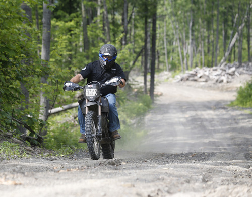 Curt Bradshaw rides his Zero FX electric motorcycle on a logging road on Tuesday, June 24, 2014, in Rotterdam, N.Y. Startups like Zero, Brammo and Mission are making state-of-the-art electric motorcycles on the West Coast. Harley-Davidson's unveiling of its prototype electric motorcycle LiveWire is likely to give a boost to smaller companies already producing plug-in bikes.  (AP Photo/Mike Groll)