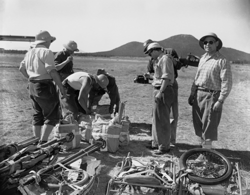 Members of Swiss mountain climbing team sort 2,000 pounds of equipment brought to aid them in search for bodies of victims of UAL plane that crashed at the Grand Canyon on June 30, shown July 6, 1956. Besides regular equipment, gear includes parachutes and wheel-equipped stretchers. Team expects to reach scene early. (AP Photo/David F. Smith)