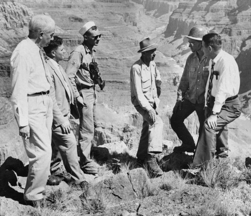Members of a congressional investigation committee talk with Colorado mountain climbers, July 8, 1956, after viewing the scene where a United Air Lines DC-7 crashed, June 30, killing 58 persons.  The UAL plane collided with a TWA Super-Constellation and both planes perished, killing a total of 128 persons.  From left to right:  mountain climbers Allen Auten, Fred Welch and David Lewis of the Colorado Mountain Climbing Club, and Congressmen Walter Rogers (D-Tex.).  Other committee members are unidentified.  The UAL crash scene is in the center of the picture.  (AP Photo)