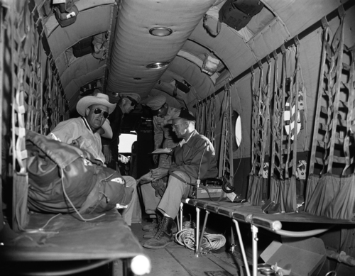 Two of twelve UAL officials selected for their experience in mountain climbing and rescue work prepare to leave for the site of UAL plane in Grand Canyon, Arizona, that crashed in this rugged country Saturday June 30, killing 58 persons, to organize recovery attempts of victims, July 3, 1956. From left: Clyde Searles, UAL C.W.O. Billy Pearson, army helicopter pilot, Lt. John Ahern, Army; and F.A. Clarke, UAL. (AP Photo/David F. Smith)