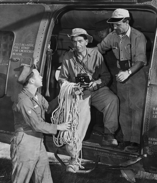 Two members of a Swiss mountain climbing team, who arrived in Grand Canyon, Arizona to assist in recovering bodies of victims of a UAL plane crash in this canyon on June 30, are handed a coil of rope by Spc/3 Robert Lee as they leave by helicopter for the wreck scene, July 6, 1956. From left are Lee, Anton Spinas, who will direct the team, and Max Stampfli, Swiss pilot. (AP Photo/David F. Smith)