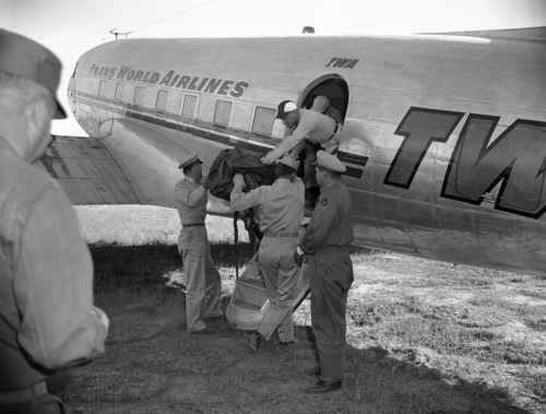 First of eight more bags containing portions of unidentified people who died in the crash of a TWA Constellation near here on Saturday, June 30, is loaded aboard a plane for flight to the coroner's office in Flagstaff in Grand Canyon, Arizona , July 3, 1956. Seven more bags are expected to be flown out from the crash where 70 died. This will complete the TWA search and four bags from the UAL crash are expected to be flown out. (AP Photo/David F. Smith)