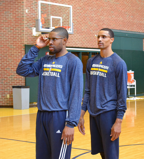 In this March 25, 2014 photo provided by Pacers.com, Indiana Pacers basketball players C. J. Watson, left, and George Hill wear Google glasses during practice at Bankers Life Fieldhouse in Indianapolis. Google Glass is slowly becoming more common in sports as teams and broadcasters try to bring fans closer to the action. (AP Photo/Pacers.com, Celeste Ballou)