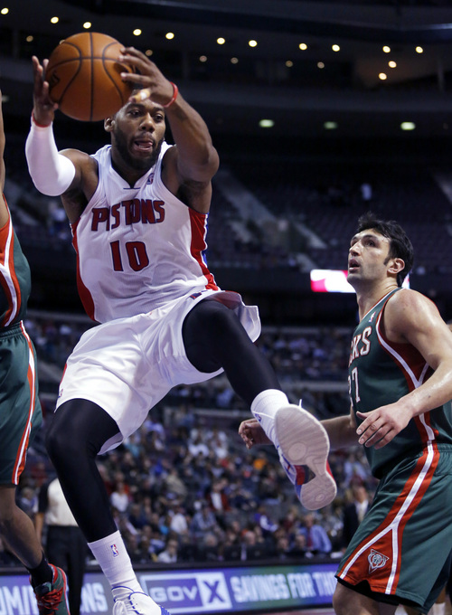 Detroit Pistons forward Greg Monroe (10) grabs one of his 14 rebounds in front of Milwaukee Bucks center Zaza Pachulia during the second half of an NBA basketball game Monday, March 31, 2014, in Auburn Hills, Mich. Monroe led the Pistons with 28 points in a 116-111 win. (AP Photo/Duane Burleson)