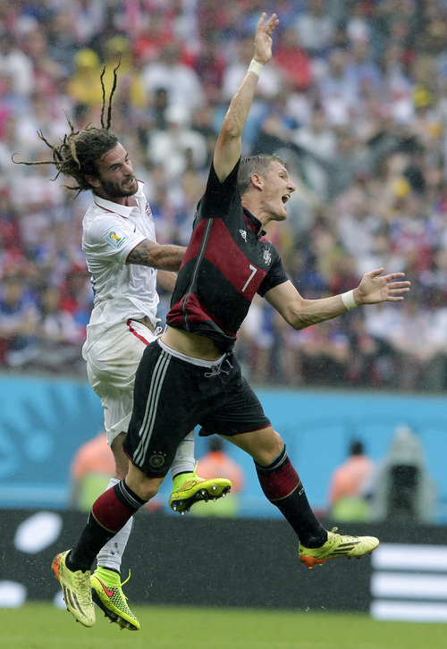 United States' Kyle Beckerman, left, makes contact with Germany's Bastian Schweinsteiger during the group G World Cup soccer match between the USA and Germany at the Arena Pernambuco in Recife, Brazil, Thursday, June 26, 2014. (AP Photo/Matthias Schrader)