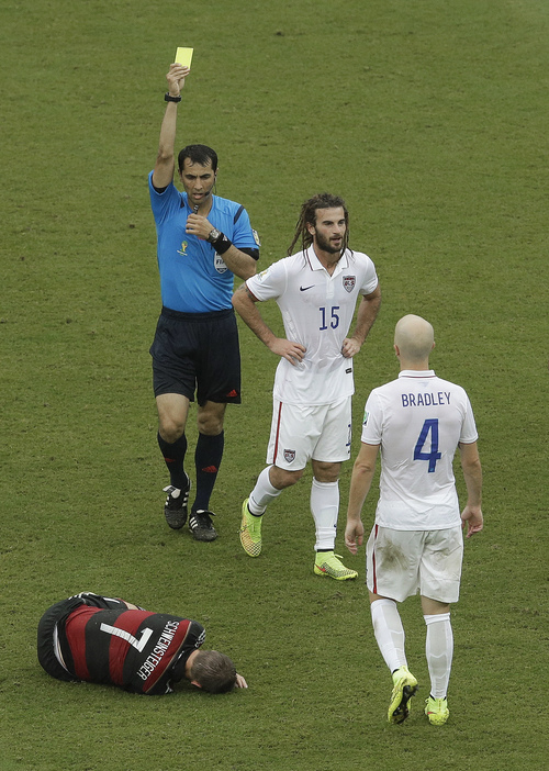 The referee gives a yellow card to United States' Kyle Beckerman (15) after his foul against Germany's Bastian Schweinsteiger (7) during the group G World Cup soccer match between the USA and Germany at the Arena Pernambuco in Recife, Brazil, Thursday, June 26, 2014. (AP Photo/Hassan Ammar)