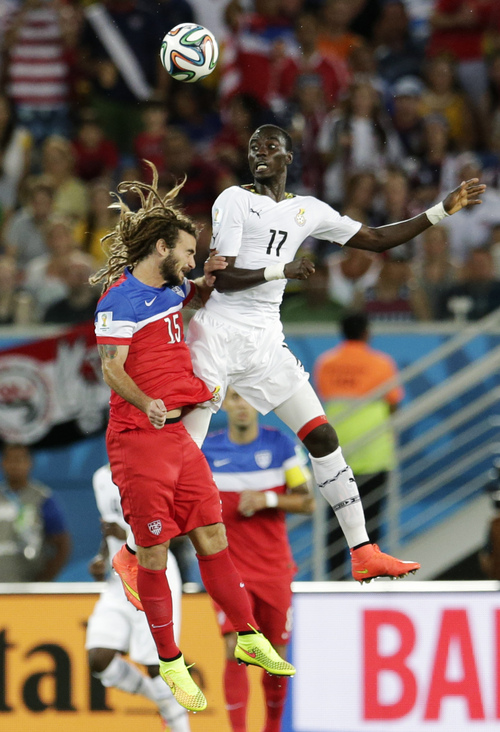 United States' Kyle Beckerman, left, goes up against Ghana's Mohammed Rabiu for a header during the group G World Cup soccer match between Ghana and the United States at the Arena das Dunas in Natal, Brazil, Monday, June 16, 2014.  (AP Photo/Petr David Josek)