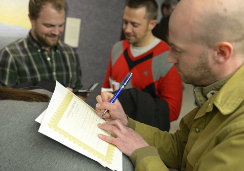 Keith Johnson | Tribune File Photo  Officiant Derek Snarr signs the marriage certificate of Jason Dautel, left and Micah Unice after they were married outside the Salt Lake County clerks office, Friday, December 20, 2013.