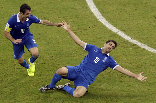 Greece's Sokratis Papastathopoulos, right, celebrates scoring his side's first goal during the World Cup round of 16 soccer match between Costa Rica and Greece at the Arena Pernambuco in Recife, Brazil, Sunday, June 29, 2014. (AP Photo/Hassan Ammar)