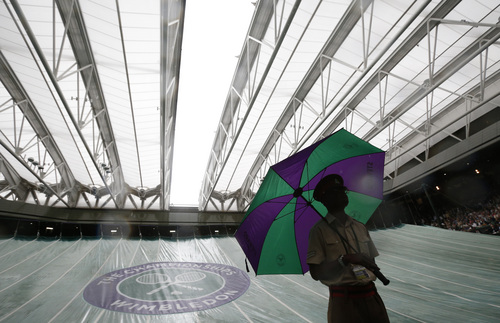 A British military steward stand with an umbrella as the roof is closed on Centre Court due to rain which led to the suspension of the women's singles match of Eugenie Bouchard of Canada against Alize Cornet of France at the All England Lawn Tennis Championships in Wimbledon, London, Monday, June 30, 2014. (AP Photo/Pavel Golovkin)