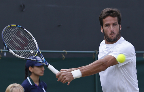 Feliciano Lopez of Spain plays a return to John Isner of the U.S. during their men's singles match at the All England Lawn Tennis Championships in Wimbledon, London, Monday, June 30, 2014. (AP Photo/Pavel Golovkin)