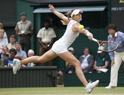 Alize Cornet of France plays a return to Eugenie Bouchard of Canada during their women's singles match at the All England Lawn Tennis Championships in Wimbledon, London, Monday, June 30, 2014. (AP Photo/Pavel Golovkin)