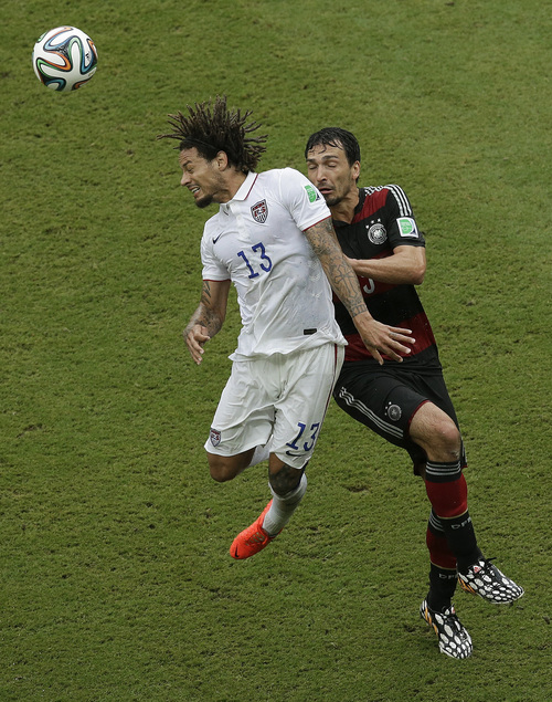 United States' Jermaine Jones (13) heads the ball past Germany's Mats Hummels during the group G World Cup soccer match between the USA and Germany at the Arena Pernambuco in Recife, Brazil, Thursday, June 26, 2014. (AP Photo/Hassan Ammar)