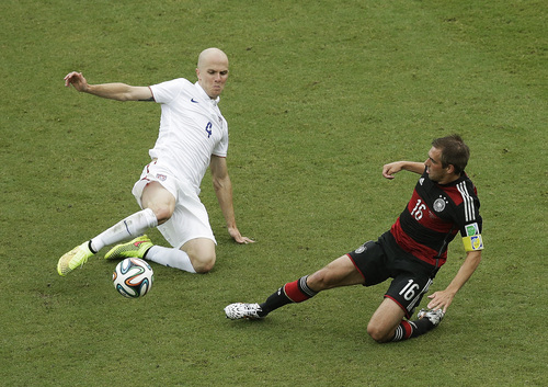 United States' Michael Bradley (4) and Germany's Philipp Lahm battle for the ball during the group G World Cup soccer match between the USA and Germany at the Arena Pernambuco in Recife, Brazil, Thursday, June 26, 2014. (AP Photo/Hassan Ammar)