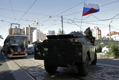 A pro-Russian fighters' APC travels near the captured Interior Ministry headquarters in Donetsk, eastern Ukraine Tuesday, July 1, 2014. The rebels captured the Interior Ministry headquarters in the city after an hours-long gun battle, a day after the president said rebels weren't serious about peace talks and ended a cease-fire. (AP Photo/Dmitry Lovetsky)