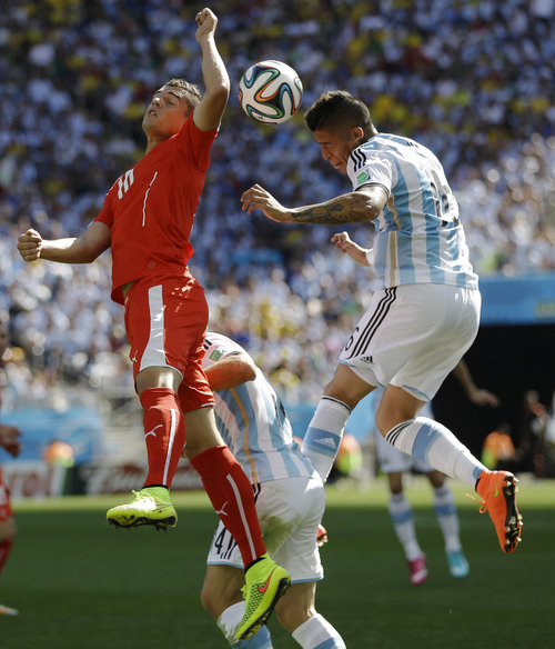 Argentina's Marcos Rojo, right, and Switzerland's Granit Xhaka go for a header during their World Cup round of 16 soccer match at the Itaquerao Stadium in Sao Paulo, Brazil, Tuesday, July 1, 2014. (AP Photo/Kirsty Wigglesworth)