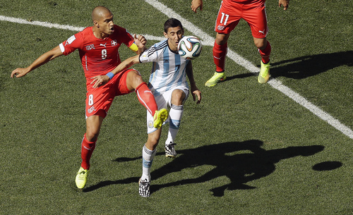Switzerland's Goekhan Inler, left, and Argentina's Angel di Maria challenge for the ball during the World Cup round of 16 soccer match between Argentina and Switzerland at the Itaquerao Stadium in Sao Paulo, Brazil, Tuesday, July 1, 2014. (AP Photo/Thanassis Stavrakis)