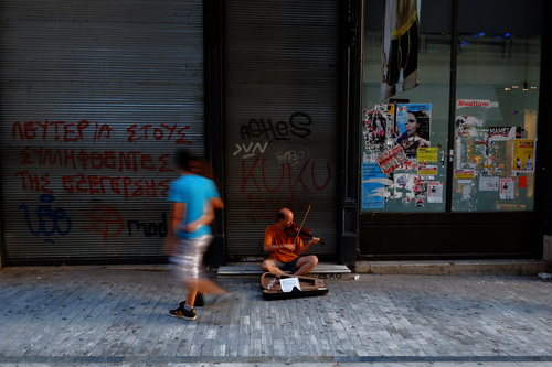 A musician plays violin as a couple walks past at a main shopping street outside of an empty closed shop in central Athens, Monday, June 30, 2014. After a crippling six-year recession lopped a quarter off the economy, Greece is expected to return to modest growth by the end of this year, according to many financial experts. The country has relied on international bailouts since it nearly went bankrupt in 2010.(AP Photo/Petros Karadjias)