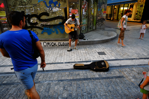 A musician plays a guitar while pedestrians listen at a main shopping street outside of an empty closed shop in central Athens, Monday, June 30, 2014. After a crippling six-year recession lopped a quarter off the economy, Greece is expected to return to modest growth by the end of this year. The country has relied on international bailouts since it nearly went bankrupt in 2010.(AP Photo/Petros Karadjias)