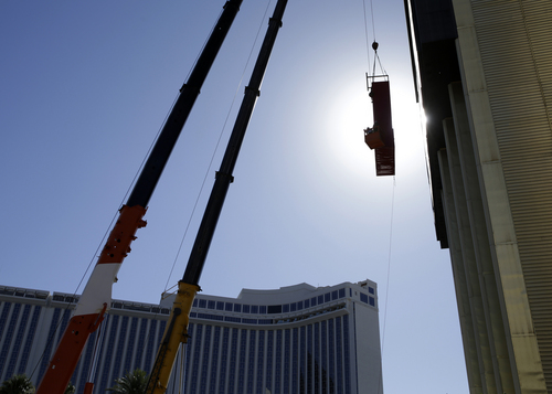 Construction workers lower part of the LVH sign Tuesday, July 1, 2014 in Las Vegas.  Westgate Resorts, a timeshare company, is the new owner of the hotel and casino.  (AP Photo/John Locher)