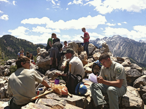 Forest Service employees supervise missionaries as they disassemble a concrete anchor atop Mount Olympus on Saturday, June 28, 2014. The missionaries had erected a flagpole in the anchor, which violates the Wilderness Act.