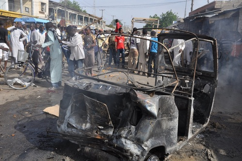 People gather at the scene of a car bomb explosion, at the central market, in Maiduguri, Nigeria, Tuesday, July 1, 2014. A car bomb exploded in a market in Nigeria's northeastern city of Maiduguri on Tuesday morning, and dozens of people are feared dead, witnesses said. They immediately blamed Boko Haram, the Islamic extremist group whose birthplace is Maiduguri and which is accused of a series of recent bomb attacks in the West African nation. (AP Photo/Jossy Ola)