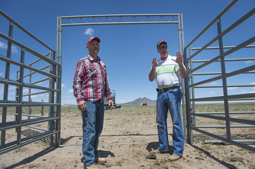 Rick Egan  |  The Salt Lake Tribune  Iron County Commissioner David Miller (left) and Beaver County Commissioner Mark Whitney (right) discuss the wild horse problem and the water corral, intended to attract and trap wild horses, on private land northwest of Cedar City, Wednesday, April 23, 2014