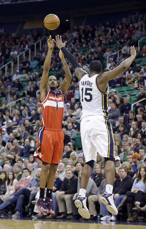 Washington Wizards' Trevor Ariza (1) shoots as Utah Jazz's Derrick Favors (15) defends in the fourth quarter during an NBA basketball game Saturday, Jan. 25, 2014, in Salt Lake City. The Jazz won 104-101. (AP Photo/Rick Bowmer)