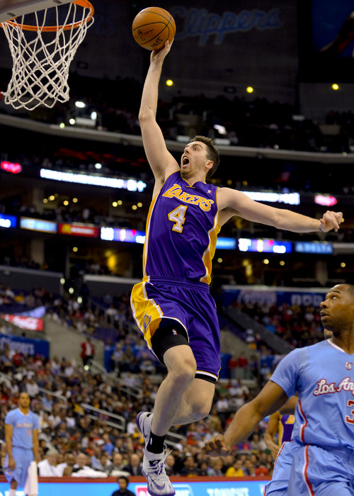 Los Angeles Lakers forward Ryan Kelly (4) goes up for a dunk as Los Angeles Clippers guard Willie Green, right, in the second half of an NBA basketball game, Sunday, April 6, 2014, in Los Angeles. The Clippers won 120-97.(AP Photo/Gus Ruelas)