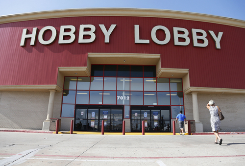 """FILE - This June 30, 2014, file photo shows customers walking into a Hobby Lobby store in Oklahoma City. There may be more to that """"we the people"""" notion than you thought.These are boom times for the concept of """"corporate personhood."""" Corporations are people? Mitt Romney got mocked during the 2012 presidential campaign for the very idea. But it turns out the principle has been lurking in U.S. law for more than a century, and the Supreme Court, in a 5-4 ruling, gave it more oomph this week when it ruled that certain businesses are entitled to exercise religious rights just as do people. (AP Photo/Sue Ogrocki, File)"""