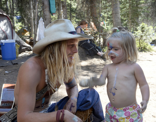 Al Hartmann  |  The Salt Lake Tribune  Cole Wardley, plays with his two-year-old daughter Juniper Rhythm Lowery in The Children's Camp at  the Rainbow Family Gathering in the Uinta Mountains 15 miles northeast of Heber.   Rainbow family members with children have their own camping area at the gathering.