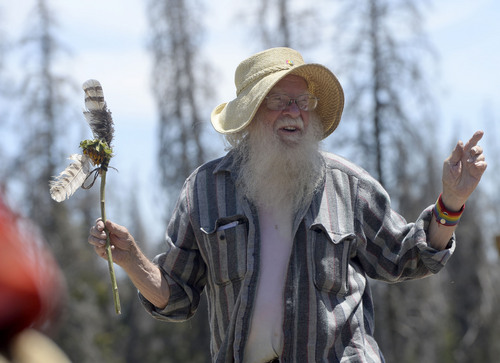 Al Hartmann  |  The Salt Lake Tribune  Elder member of  the Rainbow Family talks over camp issues in the council circle at their camp in the Uinta Mountains 15 miles northeast of Heber.  There is no one leader.  The council talks over problems calmly with the talker holding a feather.  No one is interupted.  Members of the council talk individually until a consensus is achieved.
