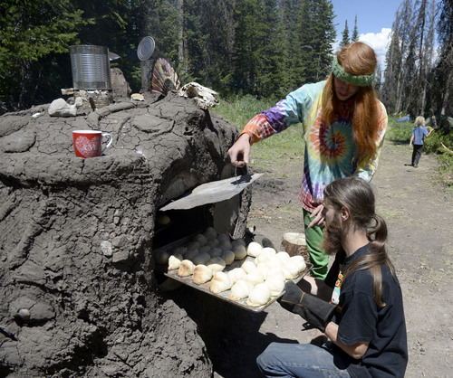 "Al Hartmann  |  The Salt Lake Tribune  ""Divine"" top and ""Red"",  apprentice bakers pull fresh rolls from wood-fired ovens made with 55-gallon oil drums built on rock frames and mud at the  Rainbow Family Gathering in the Uinta Mountains 15 miles northeast of Heber.  The ""Lovin Ovens"" take 3-4 days to construct but churn out thousands of fresh ,homemade rolls, and pizzas for attendees at the gathering."