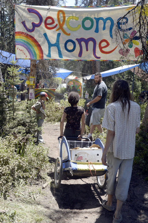 "Al Hartmann  |  The Salt Lake Tribune  Rainbow family members reach the first ""Welcome Home"" banner after walking the 2 miles into  the Rainbow Family Gathering in the Uinta Mountains 15 miles northeast of Heber."