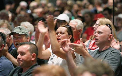 Attendees cheer as Riverside County Supervisor Jeff Stone speaks during a meeting about a plan to process immigrants detained in Texas at the Murrieta U.S. Border Patrol facility, during a meeting at the Murrieta Mesa High School auditorium Wednesday, July 2, 2014, in Murrieta, Calif. (AP Photo/The Press-Enterprise, Terry Pierson)