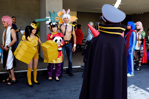 People dressed as anime characters wait for a bus to take them to the Anime Expo in Los Angeles on Friday, July 4, 2014. The Anime Expo 2014 being held at the LA Convention Center is the largest anime, manga and Japanese culture convention in North America which runs from July 3 to 6. (AP Photo/Richard Vogel)