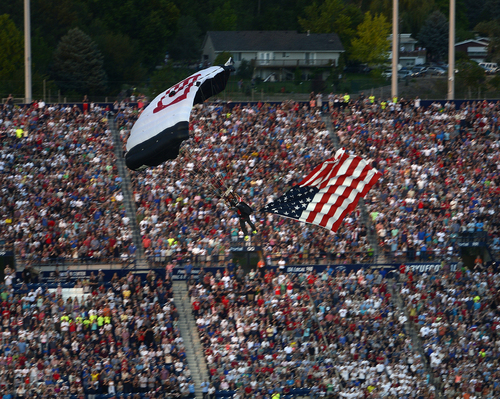 """Scott Sommerdorf      The Salt Lake Tribune A skydiver brings in the American flag at the """"Stadium of Fire"""" in Provo, Friday, July 4, 2014."""