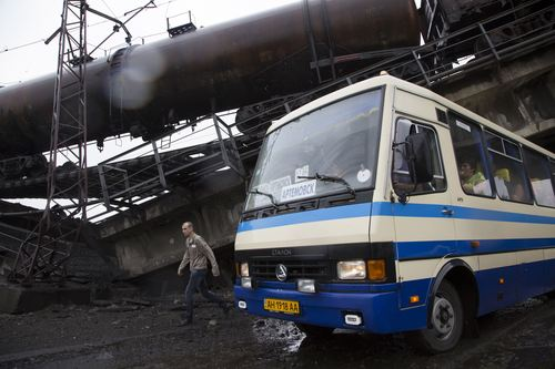 A man walks near a bus driven under a destroyed railroad bridge, near the village of Novobakhmutivka, 20 km North from the city of Donetsk, eastern Ukraine Monday, July 7, 2014. The bridge has been destroyed, blocking a key access route to the rebel-held city. (AP Photo/Dmitry Lovetsky)