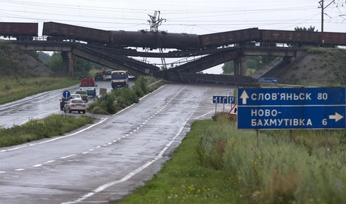 Cars queue to drive under a destroyed railroad bridge over a main road leading into the east Ukraine city of Donetsk, near the village of Novobakhmutivka, 20 km North from the city of Donetsk, eastern Ukraine Monday, July 7, 2014. The bridge has been destroyed, blocking a key access route to the rebel-held city. (AP Photo/Dmitry Lovetsky)