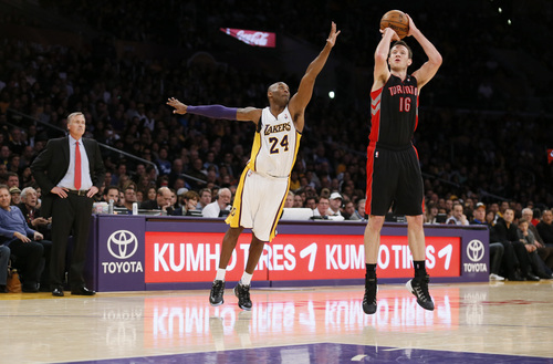 Los Angeles Lakers' Kobe Bryant attempts to block a shot from behind Toronto Raptors' Steve Novak, right, as Lakers' head coach Mike D'Antoni, left, looks on during the second half of an NBA basketball game in Los Angeles, Sunday, Dec. 8, 2013.  It was Bryant's first game back after a torn left Achilles tendon injury on April 12th and the Raptors won 106-94. (AP Photo/Danny Moloshok)