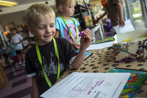 Chris Detrick  |  The Salt Lake Tribune Andrew Raymond, 4, and Abigail Raymond, 7, fill out their book report cards as a part of the Play Unplugged program at The Dog-Eared Page in Holladay Tuesday, June 24, 2014. Play Unplugged is a summer program that gives kids incentives to do other activities besides watching TV or playing video games. For every activity they complete, they receive a badge.